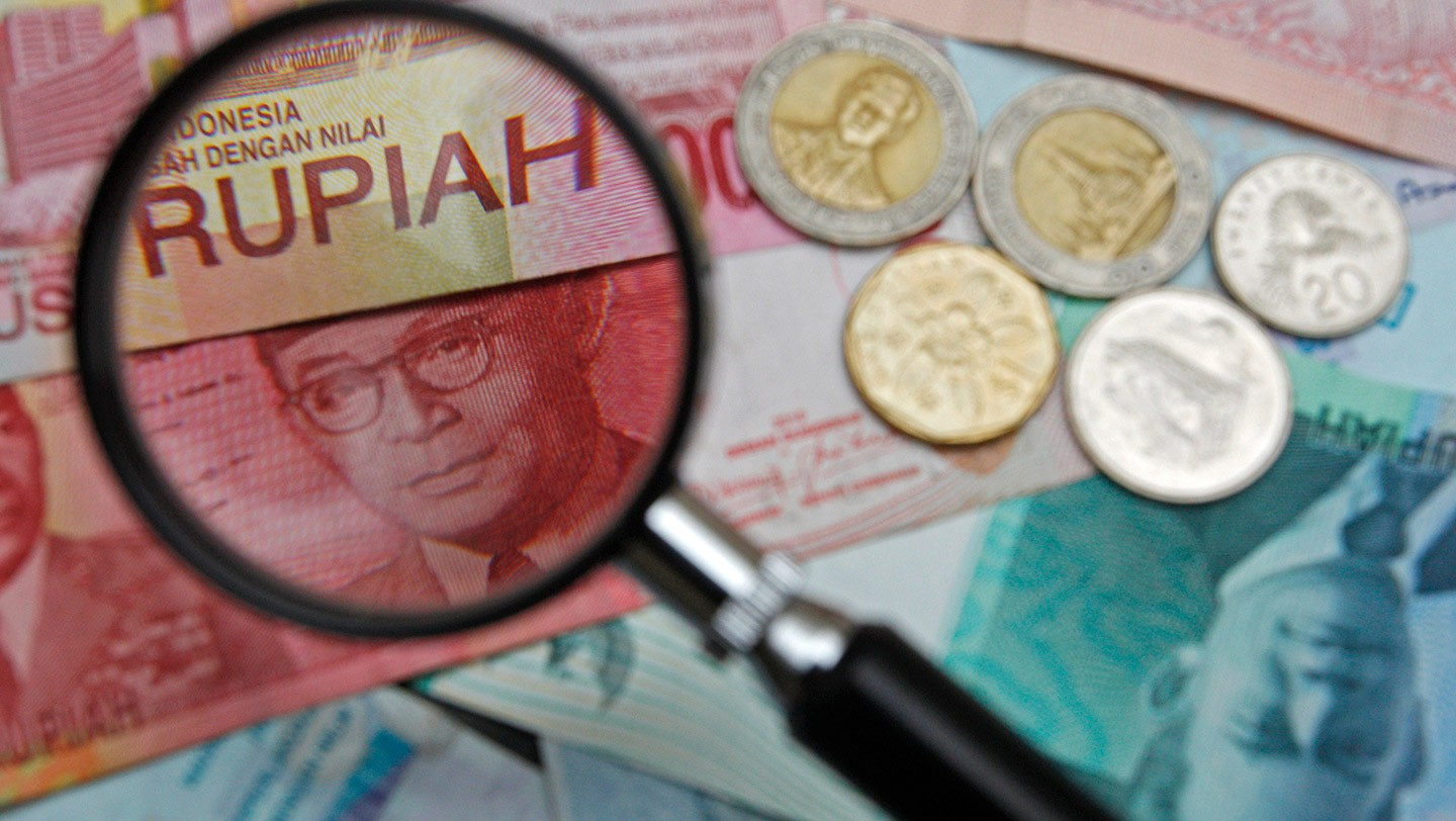 100,000 Indonesian rupiah note is seen through a magnifying glass