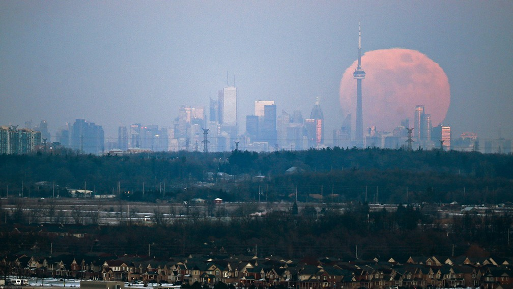 moon rises over the Toronto city skyline
