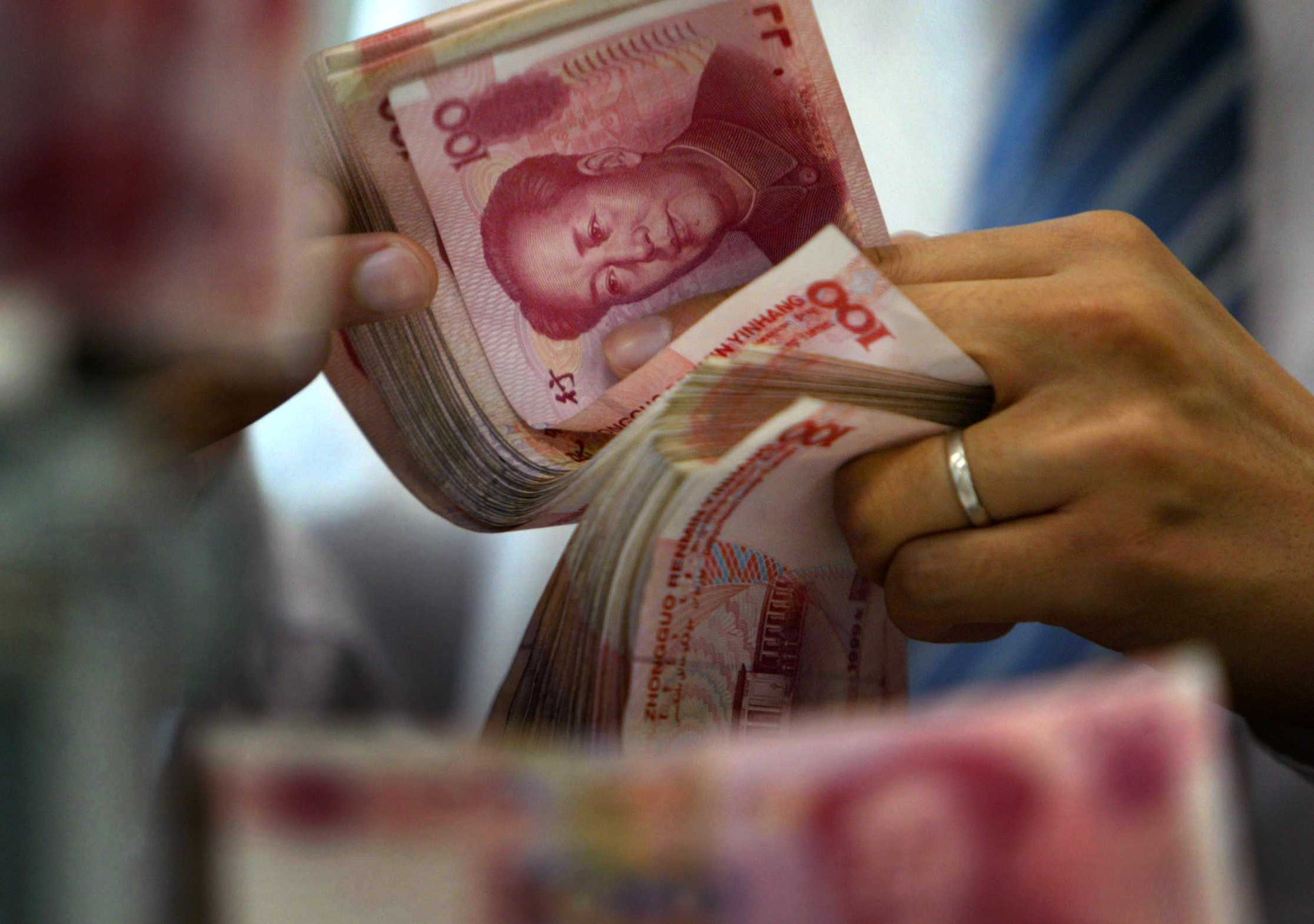 An employee counts yuan notes at a bank in Nanjing