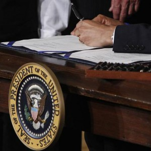 U.S. President Barack Obama signs the health insurance reform bill in the East Room at the White House in Washington