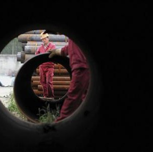Workers are seen through a steel tube at a steel products market in Hefei
