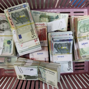 Foreign currency banknotes are placed on a basket for counting during a photo opportunity at the bank's headquarters in Seoul