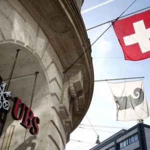 A Swiss national flag and a flag of the city of Basel fly over the entrance of a branch office of Swiss bank UBS in Basel