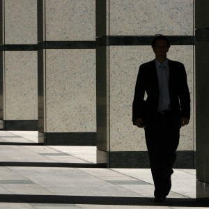 Man walks through Canary Wharf business district in London