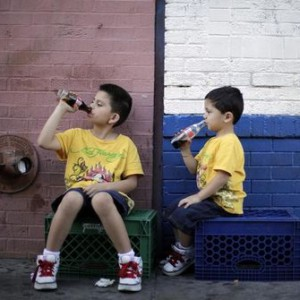 Jessie Rodriguez, 8, and his brother Christopher Rodriguez, 3, drink soda as they sit in the shade on a hot day in downtown Los Angeles