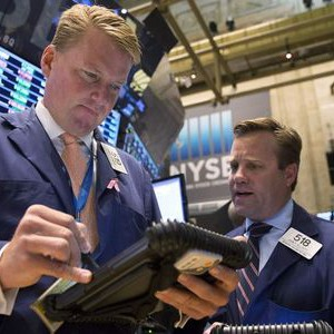 Traders John Bowers (L) and John Elliott work on the floor of the New York Stock Exchange June 19, 2014. REUTERS/Brendan McDermid