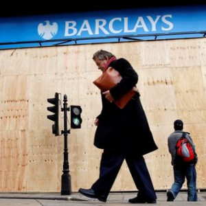Pedestrians walk past a Barclays bank logo in central London