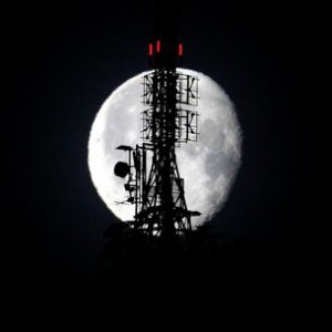The waning gibbous moon shines behind a telecommunications tower in the Swiss mountain resort of St. Moritz
