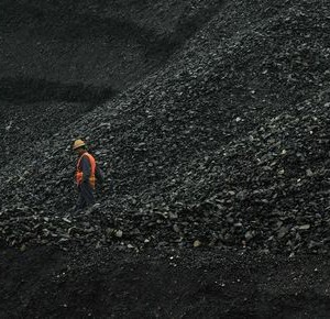 A labourer walks amid piles of coal at an opencast coal mine in Fuxin