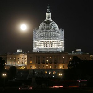 The moon is seen rising behind the dome of the U.S. Capitol building, currently undergoing renovations, in Washington