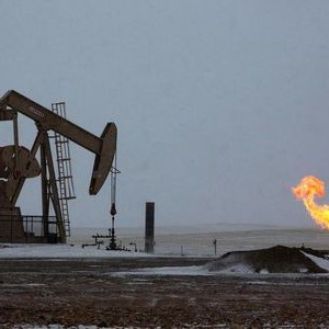 Natural gas flares are seen at an oil pump site outside of Williston