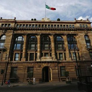 The national flag flutters atop the Bank of Mexico building in downtown Mexico City