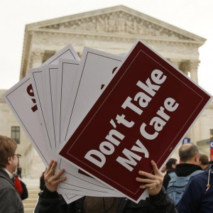 A demonstrator in favor of the Affordable Care Act hands out signs in front of the Supreme Court in Washington
