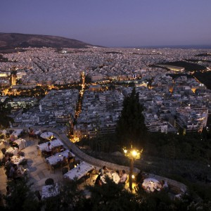People sit in a restaurant on Lycabettus hill overlooking Athens, Greece July 10, 2011.
