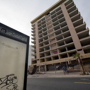Pedestrians pass an abandoned hotel in the tourist area of San Juan, Puerto Rico, July 18, 2015. Puerto Rico may sport palm trees, pristine beaches and glorious weather but its tourism industry is losing out to rival Caribbean islands - and that is holding the U.S. territory back at a time when its deeply troubled economy most needs a fillip. Hoteliers blame a variety of issues for Puerto Rico lagging in both the growth of visitors and hotel rooms: mandatory staff perks, high construction and electricity costs, as well as plenty of red tape. Picture taken July 18, 2015. REUTERS/Alvin Baez - RTX1LZJL