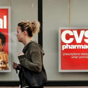 A pedestrian walks past a CVS drugstore in Boston, Massachusetts November 1, 2006. Drugstore chain CVS Corp on Wednesday agreed to acquire pharmacy benefits manager Caremark Rx Inc for $20.6 billion to expand its prescription benefits and mail-order business.   REUTERS/Brian Snyder  (UNITED STATES)