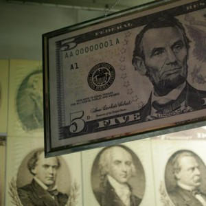An oversized five-dollar bill showing former U.S. President Abraham Lincoln is seen hanging in the printing area of the Bureau of Engraving and Printing in Washington March 26, 2015. The 150th anniversary of Lincoln's assassination at Ford's Theatre in Washington is April 15. REUTERS/Gary Cameron