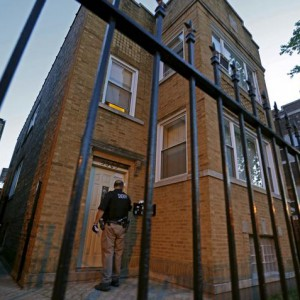 A Cook County Sheriff police officer visits a residence as he tries to serve an outstanding arrest warrant in the Austin neighborhood in Chicago, Illinois, United States, September 9, 2015.  Picture taken September 9, 2015. The focus on rounding up illegal guns, rather than low-level drug offenders, is an increasing priority for law enforcement in Chicago as murders - almost all of them with firearms and mostly related to gangs - have risen to 304 so far this year, compared with 258 in the same period last year. To match story USA-CRIME/CHICAGO-GUNS  REUTERS/Jim Young