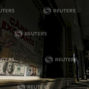 A man walks past a currency exchange office in Rio de Janeiro, Brazil, August 31, 2015. Brazil's currency and stock market both sank in opening trade on Monday after local media reported on Sunday that President Dilma Rousseff will send Congress a 2016 budget with a primary deficit after she abandoned plans to reinstate an unpopular tax to raise revenues next year. At 10:14 a.m. (1314 GMT), the Brazilian real was trading at 3.66 per dollar, about 2 percent weaker from Friday's close, while the benchmark Bovespa stock index was down about 2.2 percent. REUTERS/Ricardo Moraes