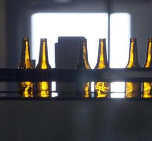 Beer bottles head for the filling machine on a conveyor belt at the Coors brewery in Golden, Colorado October 16, 2007. Brewers SABMiller and Molson Coors Brewing have agreed to combine their U.S. operations to create a business that will have annual sales of $6.6 billion and be the second-biggest market player behind Anheuser-Busch. REUTERS/Rick Wilking (UNITED STATES)