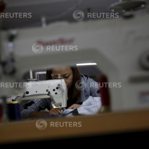 A woman works in a small-sized factory producing clothes and hats, in which more than half of its production line has stopped its operation because of a downturn in its business at the Qingyundian industrial zone in Beijing, China, October 19, 2015. China's economic growth dipped below 7 percent for the first time since the global financial crisis on Monday, hurt partly by cooling investment, raising pressure on Beijing to further cut interest rates and take other measures to stoke activity. REUTERS/Kim Kyung-Hoon