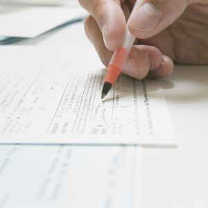 Signing a IRS tax form --- Image by © Artifacts Images/cultura/Corbis
