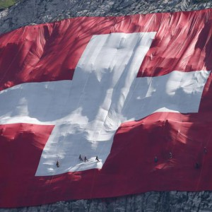 Climbers place a huge 80x80 metres (262x262 feet) Swiss national flag on the western face of the north-eastern Swiss landmark Mount Saentis, Switzerland July 31, 2015. The flag marks the Swiss National Day. REUTERS/Arnd Wiegmann