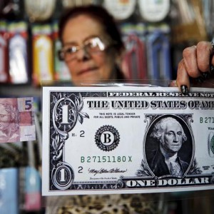 A woman holds a giant U.S. $1 banknote and a five reais banknote inside a shop, in the town of Itu, northwest of Sao Paulo, Brazil August 6, 2015. Brazil's 12-month inflation rate rose more than expected in July, to the highest in nearly 12 years, as electricity rates continued to increase sharply. A severe economic downturn and widening corruption scandal that involves dozens of lawmakers has undercut confidence in President Dilma Rousseff's leadership and raised public support for her impeachment just six months into her second term. These political tensions have dragged the Brazilian real to its weakest in more than 12 years against the U.S. dollar and prompted doomsday warnings from big investors. Picture taken August 6, 2015. REUTERS/Nacho Doce