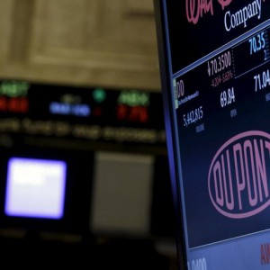 The ticker for DuPont is displayed on a screen over the floor of the New York Stock Exchange December 11, 2015. REUTERS/Brendan McDermid