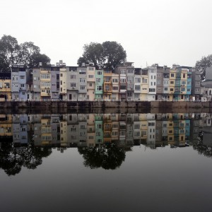 Residential houses are seen reflected on a lake in Hanoi March 6, 2014. REUTERS/Kham (VIETNAM - Tags: CITYSCAPE ENVIRONMENT) - RTR3G4E4