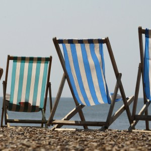 A woman sunbathes in a deckchair by the sea on a sunny day on Brighton Beach in southern England June 5, 2013.    REUTERS/Luke MacGregor (BRITAIN - Tags: ENVIRONMENT SOCIETY TRAVEL) - RTX10CH0