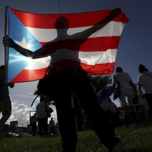 A protester holding a Puerto Rico's flag takes part in a march to improve healthcare benefits in San Juan, Puerto Rico, November 5, 2015. Tens of thousands of Puerto Ricans, including hospital workers wearing scrubs, rallied in San Juan on Thursday to press Washington to improve healthcare benefits for the indebted U.S. territory which is in the middle of a fiscal crisis. REUTERS/Alvin Baez