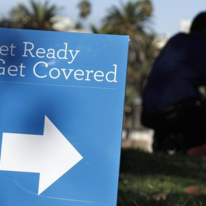 A man is silhouetted behind a sign at an Affordable Care Act outreach event hosted by Planned Parenthood for the Latino community in Los Angeles, California September 28, 2013. Enrollment for the Affordable Care Act, sometimes referred to as Obamacare, begins next week on October 1. REUTERS/Jonathan Alcorn (UNITED STATES - Tags: POLITICS HEALTH SOCIETY)