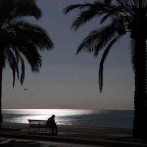 An elderly person sits and reads on the beach front along the Promenade des Anglais in Nice February 19, 2013. France's President will ask more of old people to fix the hole in the nations retirement coffers but tread gently in doing so. Even a softly-softly approach will mark the first time a left-wing president has dared to tamper with a system which is one of the sacred cows of France's model of generous welfare provision. A plan in the works will likely leave intact the official retirement age of 62 but trim annual pension rises, buying Hollande time to try and coax people in their 50s and 60s to work a few more years, officials working on the project say.    Picture taken February 19, 2013    REUTERS/Eric Gaillard (FRANCE - Tags: SOCIETY POLITICS)