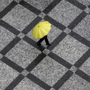 A man carrying an umbrella walks across the Old Town Square during a rainstorm in Prague May 30, 2013. Heavy rain is expected throughout central Europe this week.        REUTERS/David W Cerny (CZECH REPUBLIC - Tags: SOCIETY ENVIRONMENT TPX IMAGES OF THE DAY) - RTX1069X