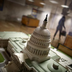 A woman walks by a miniature of the Capitol building at the Hart Senate Office Building at Capitol Hill in Washington, January 20, 2016. Members of the U.S. Congress have been spending fewer days working in Washington since the late 2000s, according to a Reuters review of congressional records going back 18 years. Picture taken January 20, 2016. To match Insight USA-CONGRESS/WORKINGDAYS  REUTERS/Carlos Barria