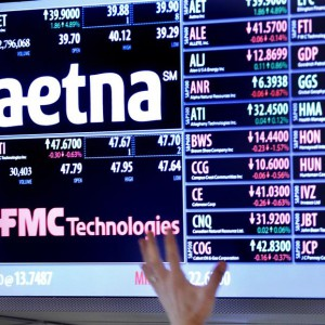 A trader points up at a display on the floor of the New York Stock Exchange August 20, 2012. Health insurer Aetna Inc said on Monday that it would buy rival Coventry Health Care Inc for $5.6 billion to increase its share of the fast-growing, U.S. government-backed Medicare and Medicaid programs. REUTERS/Brendan McDermid (UNITED STATES - Tags: BUSINESS HEALTH LOGO)
