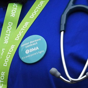 A junior doctor wears a protest badge during a strike outside St Thomas' Hospital in London, Britain February 10, 2016. English doctors staged their second 24-hour strike on Wednesday over government plans to reform pay and conditions for working anti-social hours, in a move health chiefs have warned could put patients' lives at risk.  REUTERS/Toby Melville  TPX IMAGES OF THE DAY