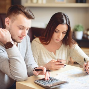 couple in home interior fill out a tax return, a budget plan