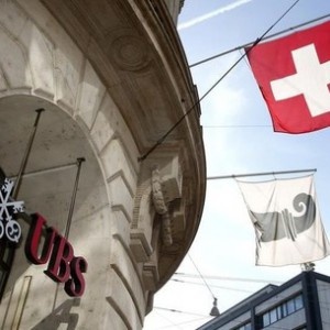 A Swiss national flag (top) and a flag of the city of Basel fly over the entrance of a branch office of Swiss bank UBS in Basel October 22, 2013. Raoul Weil, the former UBS banker wanted in the United States over allegations of helping Americans dodge taxes, appeared for a court hearing in Italy on Tuesday in the first step towards possible extradition. Weil, a Swiss citizen and former head of UBS's global wealth management business, was arrested by Italian police in Bologna on Saturday and held in the local Dozza jail.  REUTERS/Arnd Wiegmann