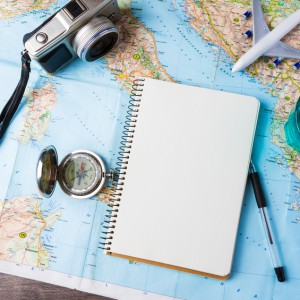 travel tourism agency table mockup tools compass, glass of water note pad, pen and toy airplane and touristic map on wooden table. Empty space you can place your text or information.