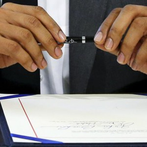 U.S. President Barack Obama prepares to sign a federal Highway Trust Fund bill into law in the Oval Office at the White House in Washington July 31, 2015. The U.S. Senate voted overwhelmingly to keep vital federal dollars flowing to road and highway projects for three more months on Thursday, averting a funding cut-off at the peak of the summer construction season.  REUTERS/Jonathan Ernst