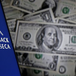 Smartphone with Mossack Fonesca logo is seen in front of a display of U.S. banknotes in this illustration taken April 11, 2016. REUTERS/Dado Ruvic/Illustration/File Photo