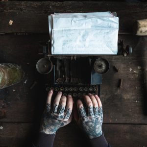 Writer with tattooed hand writing on old typing machine with blank paper,selective focus