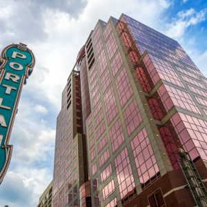 Iconic Portland sign with pink skyscraper rising next to it