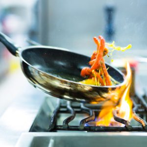 Chef in restaurant kitchen at stove with pan, doing flambe on food