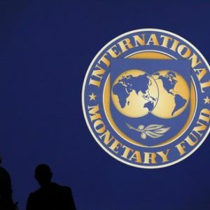Visitors are silhouetted against the logo of the International Monetary Fund at the main venue for the IMF and World Bank annual meeting in Tokyo October 10, 2012. Japan is scheduled to host the IMF and World Bank annual meetings for the first time in nearly half a century. About 20,000 people are expected to attend the event, making it one of the world's largest international conferences. REUTERS/Kim Kyung-Hoon
